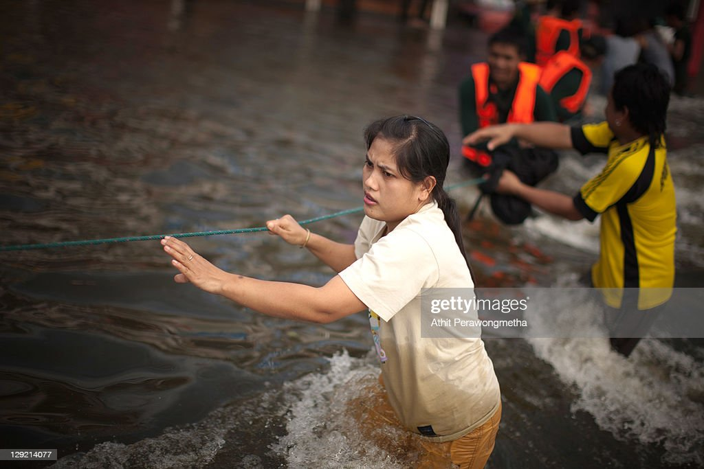 A thai woman holds a rope as she crosses a strong stream of floodwaters on October 14, 2011 in Pathum Thani, north of Bangkok,Thailand. Crews of public workers, soldiers and volunteers are evacuating residents from flooded areas north of Bangkok as efforts continue to protect the capital from increased rainfall and rising tides during the worst floods to hit the country for decades.