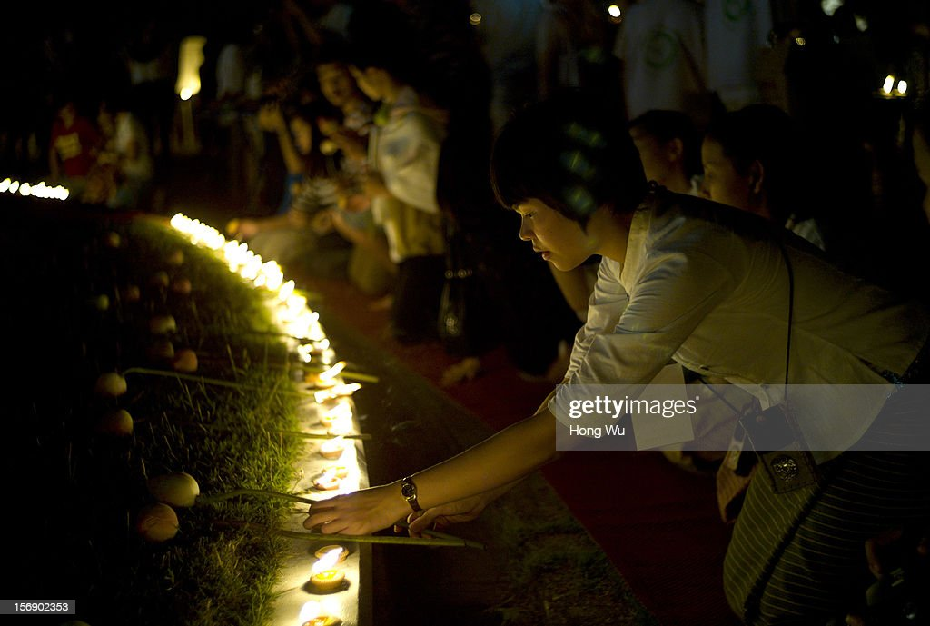 A Thai woman lights a votive candle during the Yi Peng Festival on November 24, 2012 in Chiang Mai, Thailand. The Yi Peng Festival is a traditional festival held ahead of the Loy Krathong Festival, which celebrates the full moon of the 12th lunar month in the Buddhist calendar. During the festival floating lanterns are launched into the night sky in the belief that grief and misfortune will fly away with the lanterns.