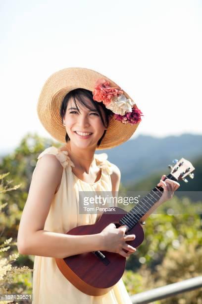 Thai woman playing ukulele outdoors