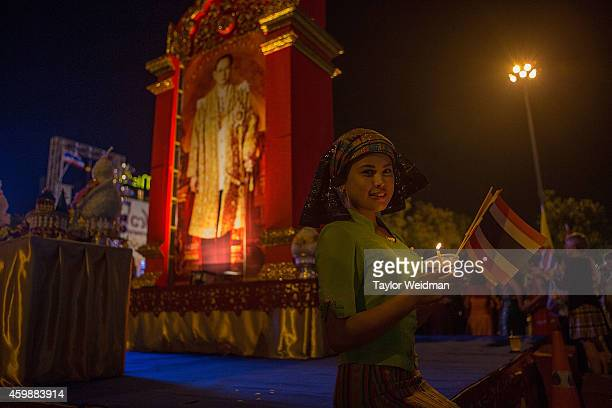 Thai woman poses in front of a picture of the King during a parade and ceremony in honor of the King's birthday on December 3 2014 in Chiang Mai...