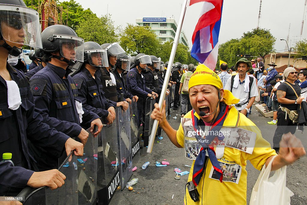 A Thai woman professes her love for Bhumibol Adulyadej, the King of Thailand, in front of riot police during a large anti government protest on November 24, 2012 in Bangkok, Thailand. The Siam Pitak group, which sponsored the protest, cited alleged government corruption and anti-monarchist elements within the ruling party as grounds for the protest. Police used tear gas and baton charges againt protesters.