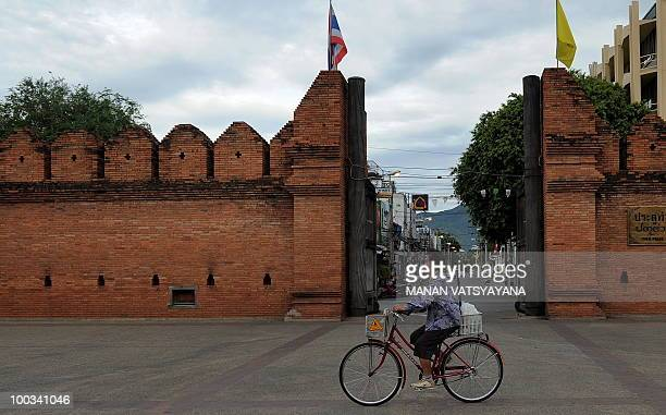 A Thai woman rides her bicycle past the Tha Phae gate in Chiang Mai some 700kms from Bangkok on May 23 2010 Thailand's Prime Minister Abhisit...