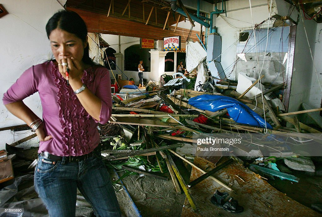 Thai woman walks by the devastation at a hotel along Patong Beach one of the worst hit provinces December 27 2004 in Phuket Thailand A tsunami caused...