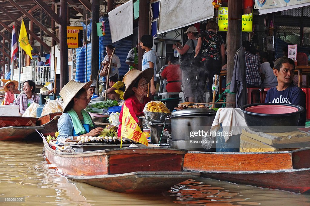 Thai women cook food on their boats while stationed on the bank of the canal in floating market on October 13 in Damnoen Saduak, Thailand. Damnoen Saduak is a district in the province of Ratchaburi in central Thailand. The central town has become a tourist attraction with its famous floating market.