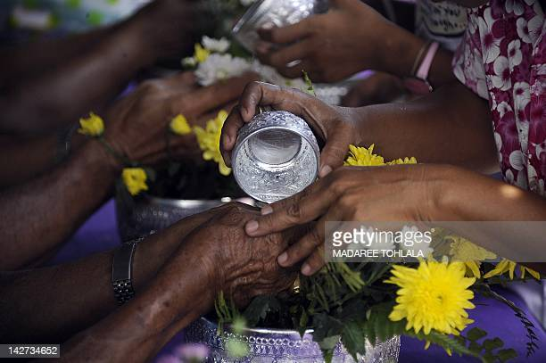 Thai women pour water on the hands of elderly people as part of traditional celebrations of the Songkran festival marking the Thai new year in...