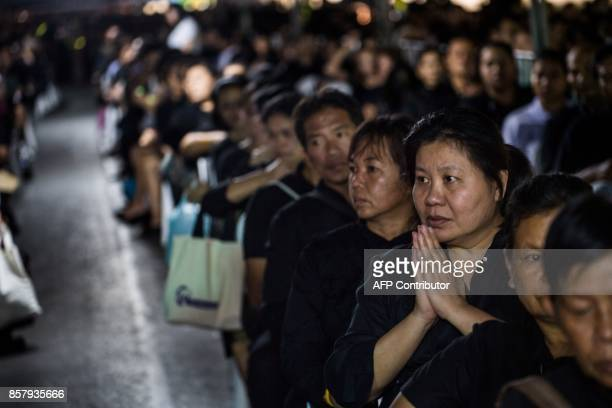 A Thai women prays while waiting with others in the periphery of the Grand Palace in Bangkok on October 5 2017 on the last day that Thai authorities...