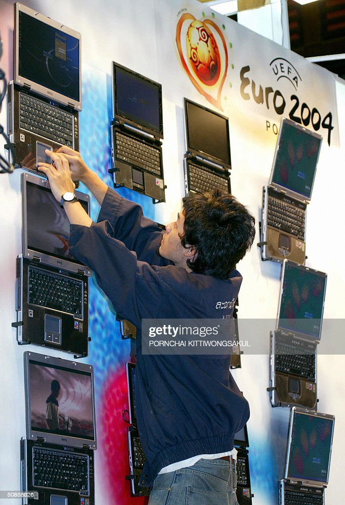 A Thai worker adjusts nootbook computers on display at the annual computer fair in Bangkok, 20 May 2004. More than 300 computer brandname companies display their new technology to urge the computer market in Thailand. AFP PHOTO/Pornchai KITTIWONGSAKUL