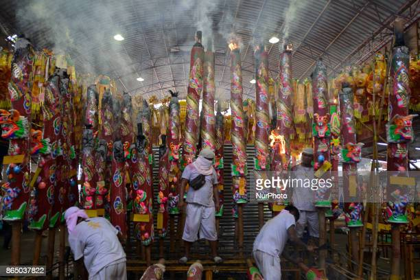A Thai worker installs a giant incense stick at Joe Sue Kung Shrine Chinese temple in Bangkok Thailand on 22 October 2017 The festival celebrates the...