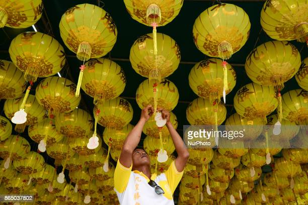A Thai worker installs a light at Wat Mangkon Kamalawat in Bangkok Thailand on 22 October 2017 The festival celebrates the local Chinese community's...