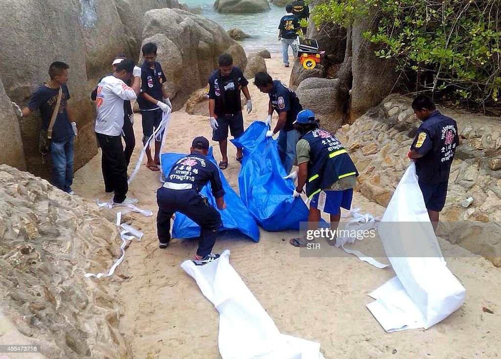 Thai workers carry the bodies of two British tourists on Koh Tao island in the Surat Thani province of southern Thailand on September 15 2014 The...