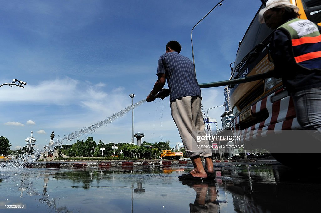 Thai workers clean roads inside the Red Shirts anti-government protestors camp at the Lumpini Park in Bangkok on May 20, 2010. The top Thai protest leader urged supporters of the anti-government 'Red Shirt' movement to refrain from violence after riots in the capital, saying 'democracy cannot be built on revenge.'