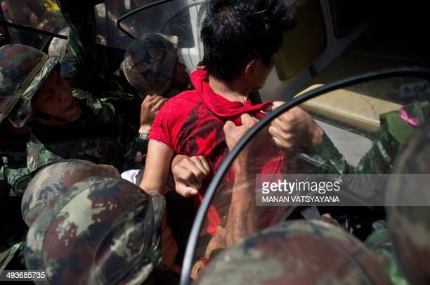 Thaiarmy soldiers take away an alleged RedShirt protester ahead of a planned gathering in Bangkok on May 24 2014 Thailand's military junta said it...
