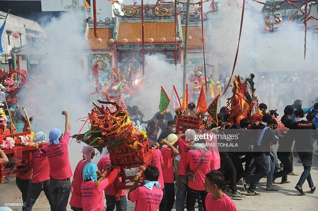 Thai-Chinese devotees carry a shrine as fire-crackers explode during an annual religious festival at Chao Mae To Mo in the Sungai Kolok district of Thailand's southern province of Narathiwat on April 29, 2016. The Chao Mae To Mo goddess who is believed to possess magic power is celebrated during the festival taking place in Narathiwat and other southern provinces. / AFP / MADAREE