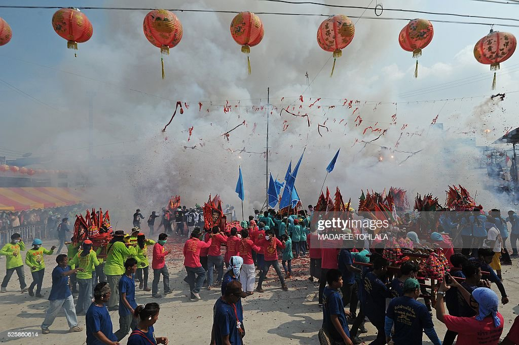 Thai-Chinese devotees carry shrines as fire-crackers explode during an annual religious festival at Chao Mae To Mo in the Sungai Kolok district of Thailand's southern province of Narathiwat on April 29, 2016. The Chao Mae To Mo goddess who is believed to possess magic power is celebrated during the festival taking place in Narathiwat and other southern provinces. / AFP / MADAREE