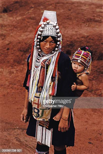 Thailand, Akha tribal villager carrying son (2-3) on back, portrait
