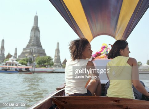 Thailand, Bangkok, Chao Phraya River,  two tourists on boat, rear view