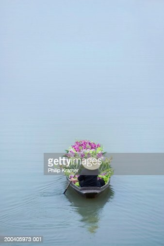 Thailand, Bangkok, vendor in boat filled with flowers, rear view