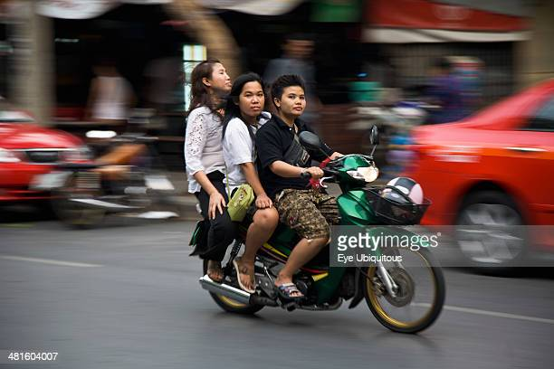 Thailand Bangkok Young Thai women on motorcycle without helmets helmet in shopping basket blurred motion