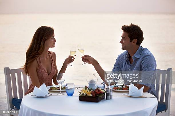 Thailand, Couple eating at table on tropical beach
