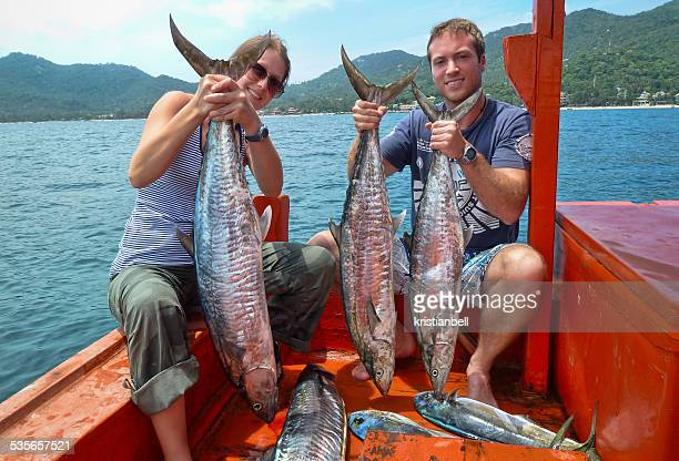Thailand, Koh Tao, Mahi Mahi, Portrait of couple on boat holding catch of fish