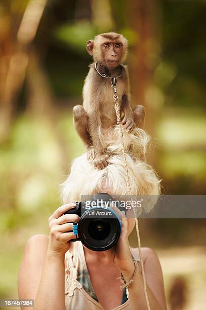 Thailand, Portrait of female photographer with macaque monkey sitting atop her head