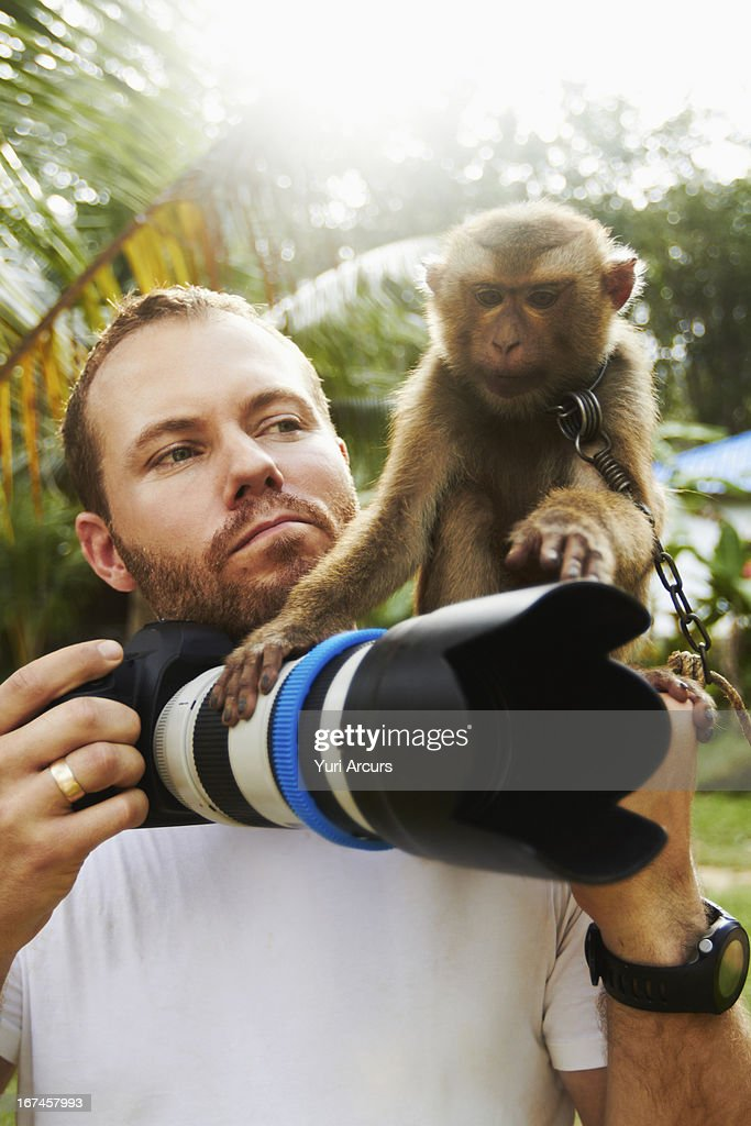 Thailand, Portrait of man with camera and macaque monkey