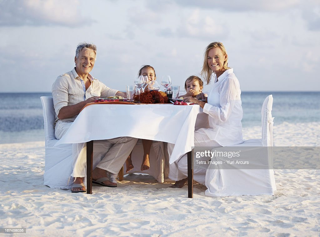 Thailand, Portrait of parents with daughters (8-9), (4-5) sitting at table on beach : Stock Photo