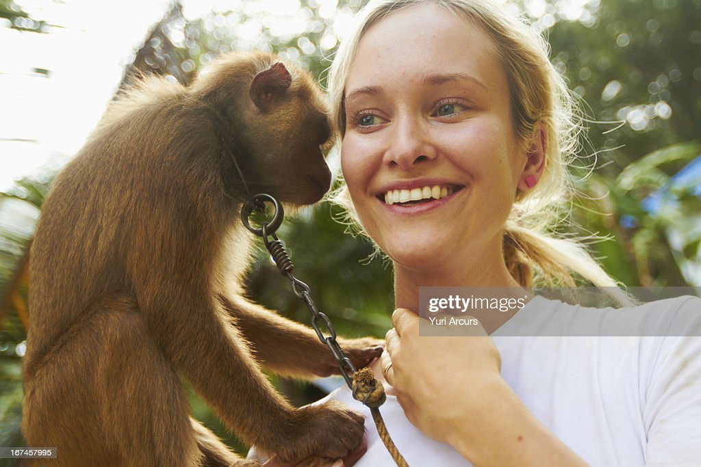 Thailand, Portrait of young woman holding macaque monkey