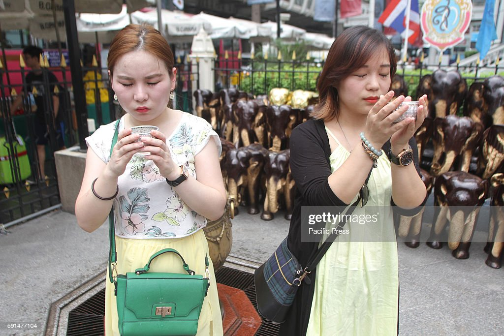 Thailand tourists and foreigners together washing with water mantra at Erawan Shrine Ratchaprasong during the anniversary of BKK bombing on the...