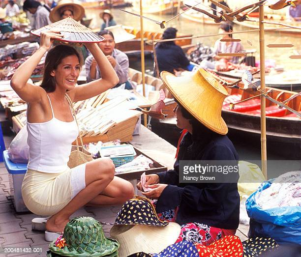 Thailand, woman trying on hat at market stall, outdoors
