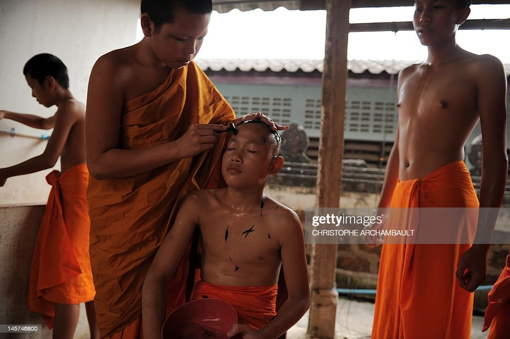 STORY 'Thailand-religion-society-gender' by Janesara FUGAL This picture taken on June 15, 2011 shows Buddhist novice monk and aspiring ladyboy Pipop Thanajindawong (R) watching as another novice gets a a twice-monthly head shave in a backyard of the Wat Kreung Tai temple, in Thailand's northern border town of Chiang Khong. The Kreung Tai temple has run a course to teach masculinity to boys who are 'katoeys', the Thai term for transsexuals or ladyboys, aged between 11 and 18 since 2008. AFP PHOTO/Christophe ARCHAMBAULT