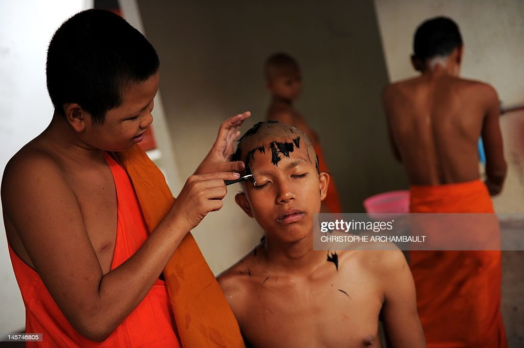 STORY 'Thailand-religion-society-gender' by Janesara FUGAL This picture taken on June 15, 2011 shows Buddhist novice monk and aspiring ladyboy Pipop Thanajindawong (C) getting a twice-monthly head shave in a backyard of the Wat Kreung Tai temple, in Thailand's northern border town of Chiang Khong. The Kreung Tai temple has run a course to teach masculinity to boys who are 'katoeys', the Thai term for transsexuals or ladyboys, aged between 11 and 18 since 2008. AFP PHOTO/Christophe ARCHAMBAULT