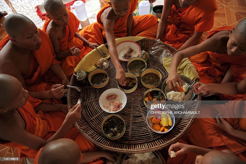 STORY 'Thailand-religion-society-gender' by Janesara FUGAL This picture taken on June 16, 2011 shows Buddhist novices having breakfast made of donations they collected earlier nearby, at the Wat Kreung Tai temple, in Thailand's northern border town of Chiang Khong. The Kreung Tai temple has run a course to teach masculinity to boys who are 'katoeys', the Thai term for transsexuals or ladyboys, aged between 11 and 18 since 2008. AFP PHOTO/Christophe ARCHAMBAULT
