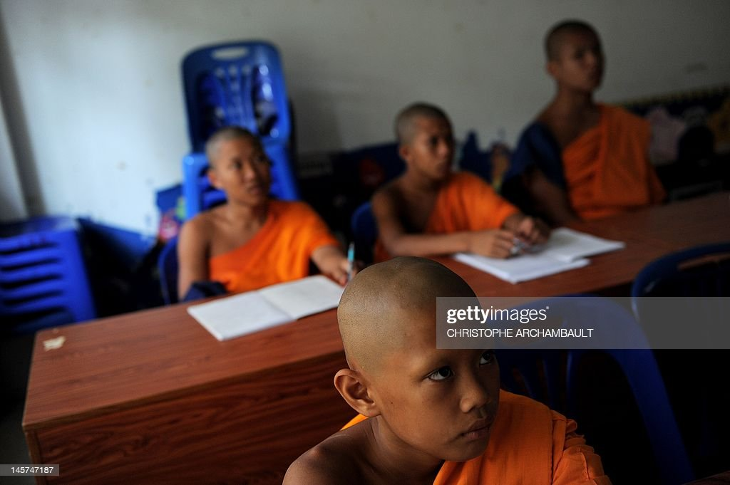 STORY 'Thailand-religion-society-gender' by Janesara FUGAL This picture taken on June 16, 2011 shows Buddhist novice monks listening during a lesson at the Wat Kreung Tai temple, in Thailand's northern border town of Chiang Khong. The Kreung Tai temple has run a course to teach masculinity to boys who are 'katoeys', the Thai term for transsexuals or ladyboys, aged between 11 and 18 since 2008. AFP PHOTO/Christophe ARCHAMBAULT