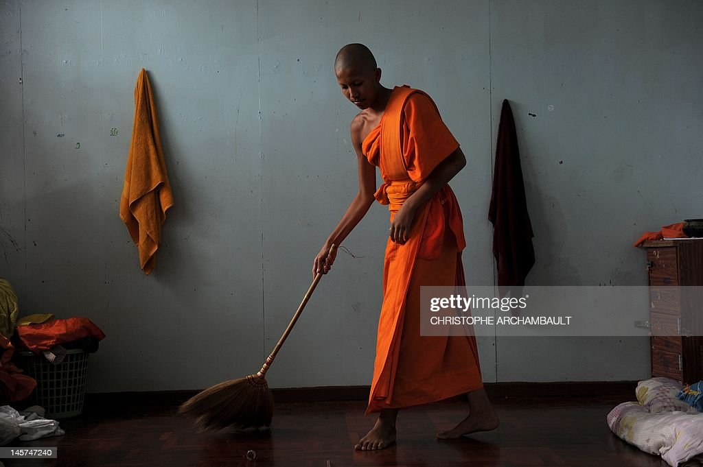 STORY 'Thailand-religion-society-gender' by Janesara FUGAL This picture taken on June 16, 2011 shows Buddhist novice monk and aspiring ladyboy Pipop Thanajindawong sweeping his shared room at the Wat Kreung Tai temple, in Thailand's northern border town of Chiang Khong. The Kreung Tai temple has run a course to teach masculinity to boys who are 'katoeys', the Thai term for transsexuals or ladyboys, aged between 11 and 18 since 2008. AFP PHOTO/Christophe ARCHAMBAULT