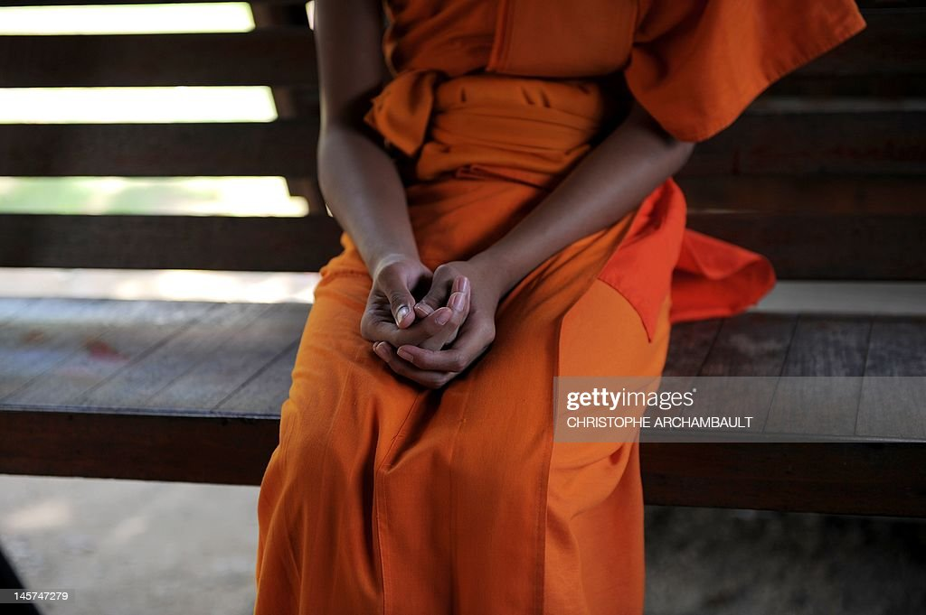 STORY 'Thailand-religion-society-gender' by Janesara FUGAL This picture taken on June 16, 2011 shows Buddhist novice monk and aspiring ladyboy Pipop Thanajindawong's hands as he sits on a bench at the Wat Kreung Tai temple, in Thailand's northern border town of Chiang Khong. The Kreung Tai temple has run a course to teach masculinity to boys who are 'katoeys', the Thai term for transsexuals or ladyboys, aged between 11 and 18 since 2008. AFP PHOTO/Christophe ARCHAMBAULT