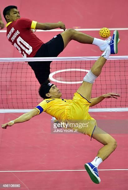 Thailand's Anuwat Chaichana strikes the ball against Malaysia's Mohd Zamree Bin Mohd Dahan in the men's team sepaktakraw semifinal match during the...