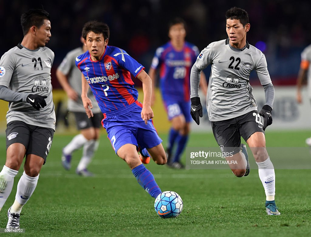 Thailand's Chonburi FC midfielder Pokklawa A Nan (R) dribbles the ball beside Japan's FC Tokyo midfielder Takuji Yonemoto (C) during the AFC champions league play-off match in Tokyo on February 9, 2016. AFP PHOTO / TOSHIFUMI KITAMURA / AFP / TOSHIFUMI KITAMURA