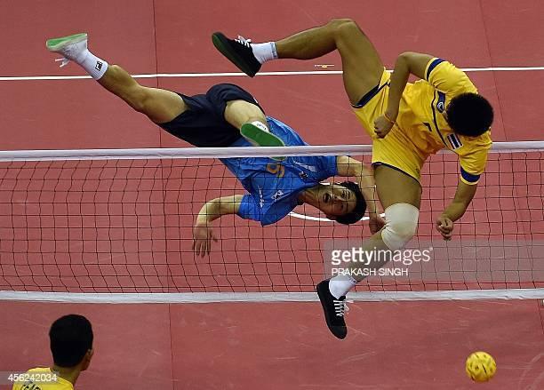 Thailand's Kaokaew Pornchai strikes the ball as South Korea's Kim Youngman defends in their men's team sepaktakraw final during the 2014 Asian Games...