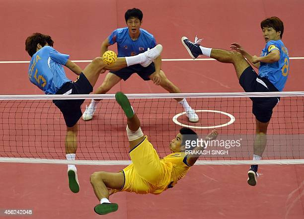 Thailand's Kaokaew Pornchai strikes the ball as South Korea's Shim Jaechul Kim Youngman and Sin Sungtae try to block in their men's team sepaktakraw...