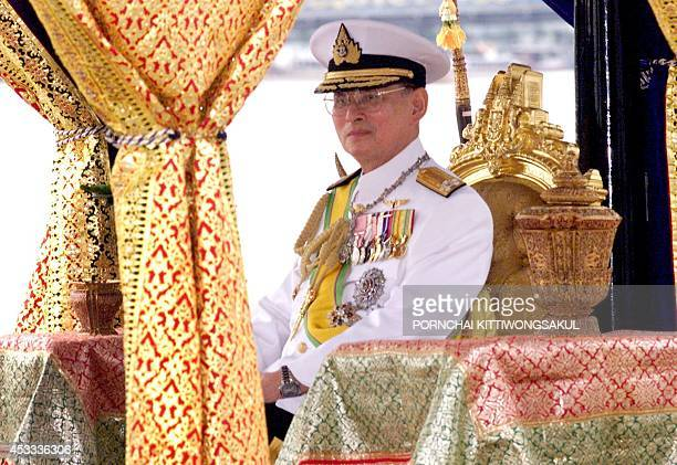 Thailand's King Bhumibol Adulyadej sits in a barge in front of a colourful waterborne on the river Chao Phraya in Bangkok 04 November 1999 The royal...