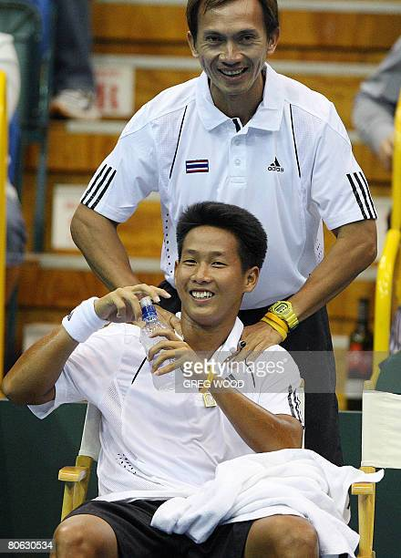 Thailand's Kirati Siributwong laughs as team captain Thanakorn Srichaphan massages him after he had won his only game of the match against...