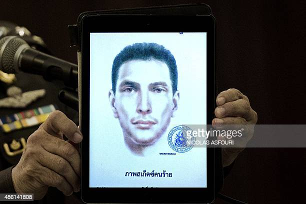 Thailand's national police spokesman Prawut Thavornsiri holds a tablet displaying a picture of an unnamed foreign man wanted by the police at the...