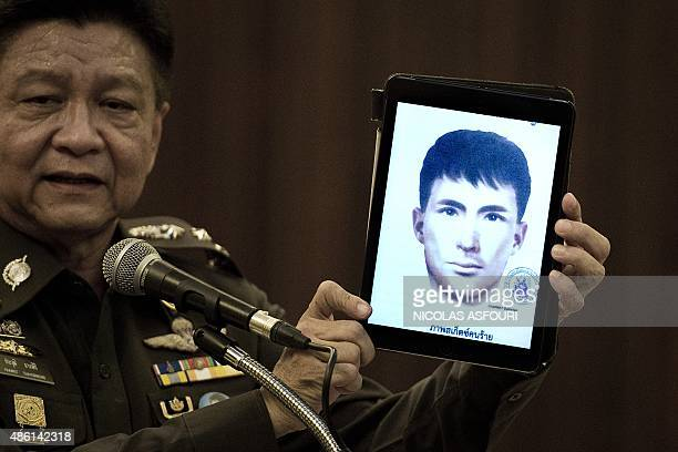 Thailand's national police spokesman Prawut Thavornsiri holds a tablet displaying a picture of Ali Jolan a foreign man wanted by the police at the...