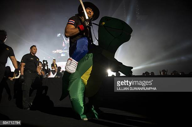 Thailand's ONE FC MMA fighter Shannon Wiratchai approaches the octagon wearing an inflated dinosaur costume during the first ever ONE FC event in...