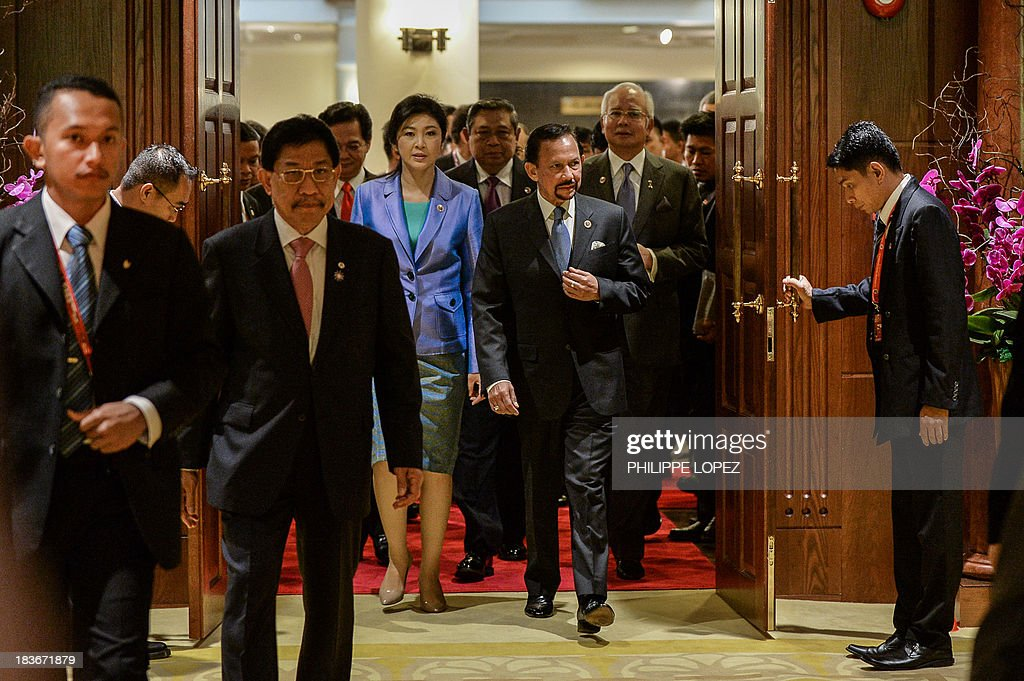 Thailand's Prime Minister Yingluck Shinawatra (back L) and Brunei's Sultan Hassanal Bolkiah (R) arrive at the 23rd summit of the Association of Southeast Asian Nations (ASEAN) in Bandar Seri Begawan on October 9, 2013, Festering territorial disputes provided the backdrop for an Asian summit kicking off on October 9 with China flexing its diplomatic muscle in the absence of a grounded US President Barack Obama.