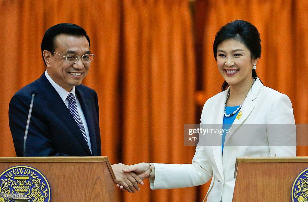 Thailand's Prime Minister Yingluck Shinawatra (R) and China's Premier Li Keqiang shake hands after addressing reporters at the government house in Bangkok on October 11, 2013. Li is visiting Thailand from October 11 - 13. AFP PHOTO / POOL / Damir Sagolj
