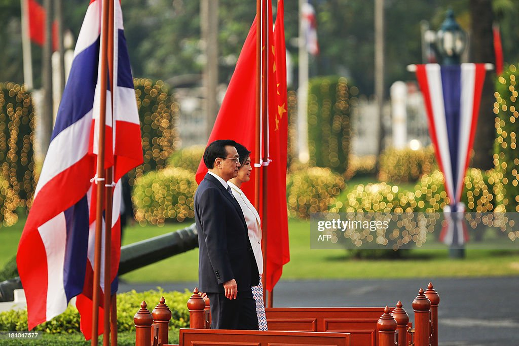 Thailand's Prime Minister Yingluck Shinawatra (R) and China's Premier Li Keqiang listen to national anthems during a welcoming ceremony at the government house in Bangkok on October 11, 2013. Li is visiting Thailand from October 11 - 13. AFP PHOTO / POOL / Damir Sagolj