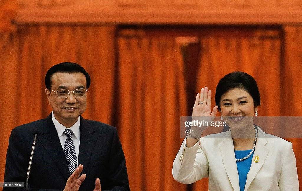Thailand's Prime Minister Yingluck Shinawatra (L) and China's Premier Li Keqiang greet reporters after addressing them at the government house in Bangkok on October 11, 2013. Li is visiting Thailand from October 11 - 13. AFP PHOTO / POOL / Damir Sagolj