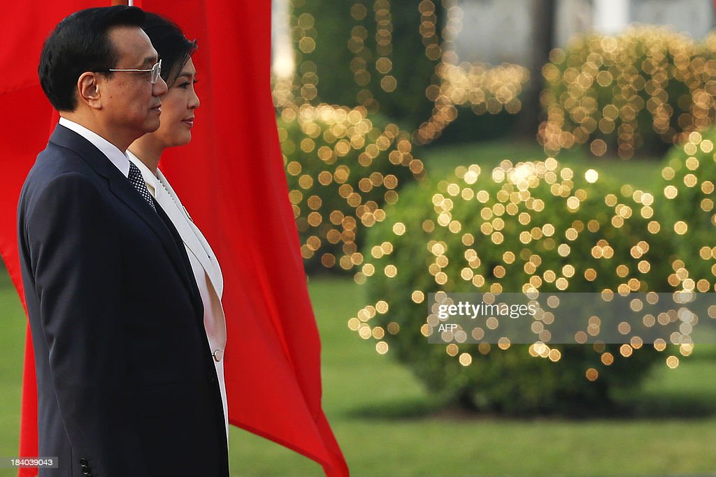 Thailand's Prime Minister Yingluck Shinawatra (R) and her Chinese counterpart Li Keqiang listen to national anthems during a welcoming ceremony at government house in Bangkok on October 11, 2013. Li is visiting Thailand from October 11 - 13. AFP PHOTO / POOL / Damir Sagolj